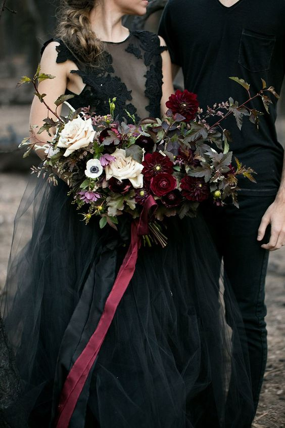 a chic wedding bouquet with dark foliage, deep red and blush blooms plus burgundy ribbons