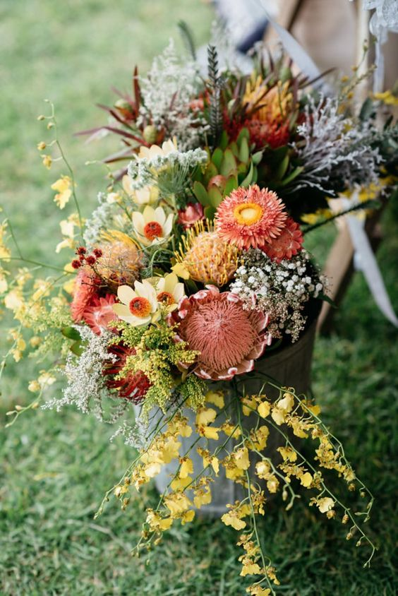 a gorgeous fall floral arrangement in a bucket with the shades of yellow, burgundy, red and green