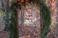 07 a lush fall woodland wedding arch covered with fir branches and lush blooms on top