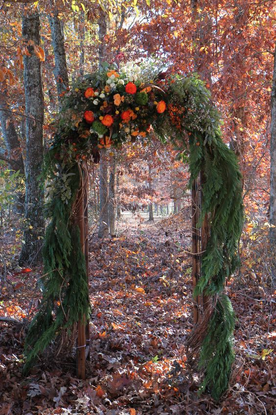 a lush fall woodland wedding arch covered with fir branches and lush blooms on top