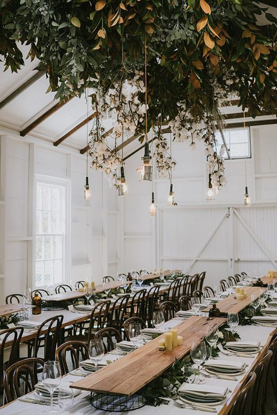 a lush foliage wedding decoration with cotton branches and bulbs hanging down