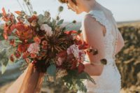 07 a moody lush bridal bouquet with rust, red, burgundy, pink blooms and textural greenery and colored ribbons