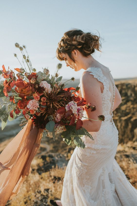 a moody lush bridal bouquet with rust, red, burgundy, pink blooms and textural greenery and colored ribbons