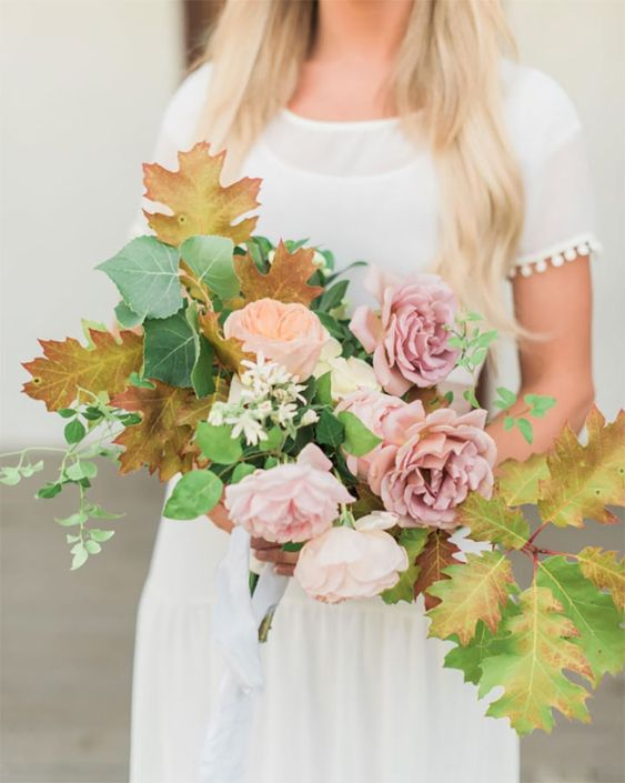 a wedding bouquet of pink roses and fall leaves of a unique and creative shape