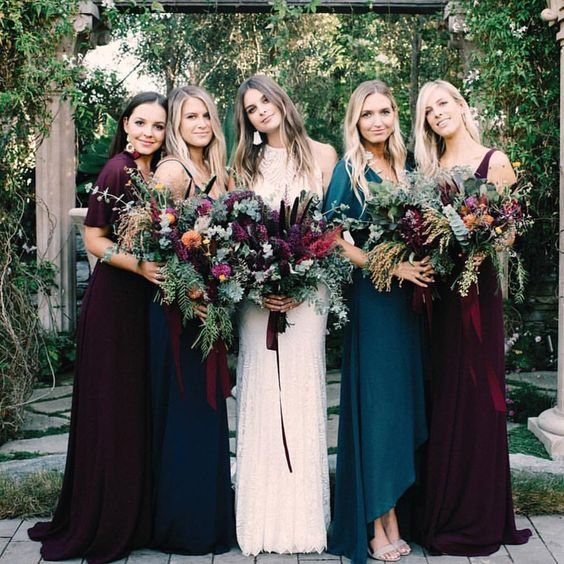 all mismatched bridesmaids' looks in plum and teal dresses to show off the personal style of each girl
