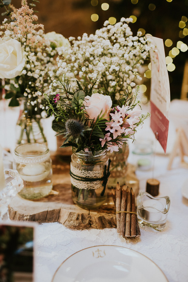 The tablescape was done with lush florals and some rustic touches like rough edge wood boards
