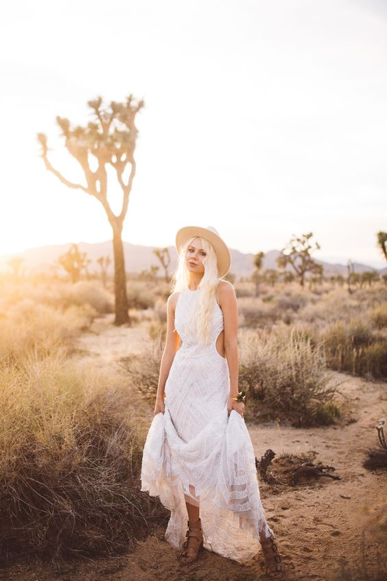 a boho lace wedding dress with side cutouts, tan strappy shoes and a neutral hat for a boho feel