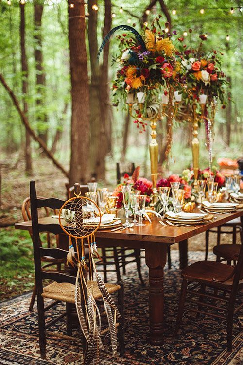 a boho woodland wedding reception done in jewel tones, with feathers and gold touches for a refined feel