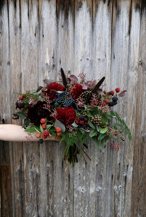 a chic Halloween bouquet with dark burgundy and red blooms and lots of berries