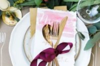 08 a chic place setting with gold rimmed plates and cutlery, with a lush greenery table runner with brigth touches