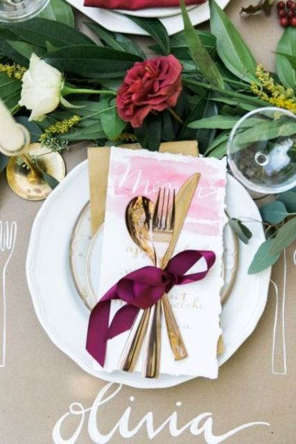 a chic place setting with gold rimmed plates and cutlery, with a lush greenery table runner with brigth touches