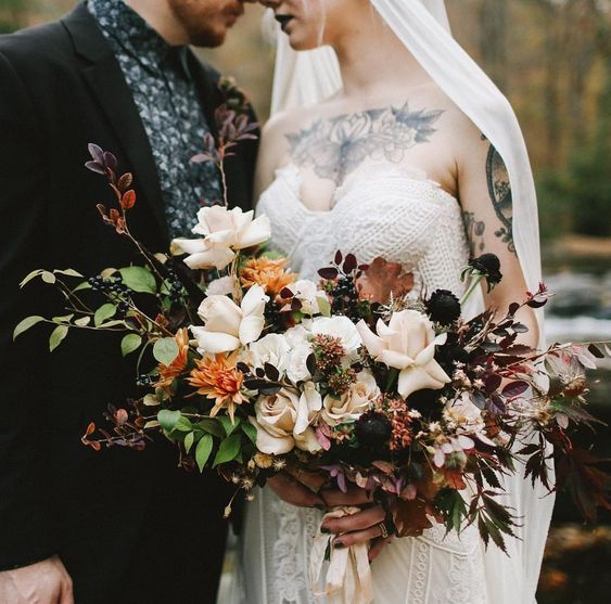 a gorgeous moody bouquet with white and almost black blooms, berries and burudungy leaves for a fall feel