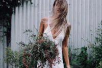 08 a modern bride in a slip wedding dress, with loose hair and a bouquet of greenery for a relaxed feel