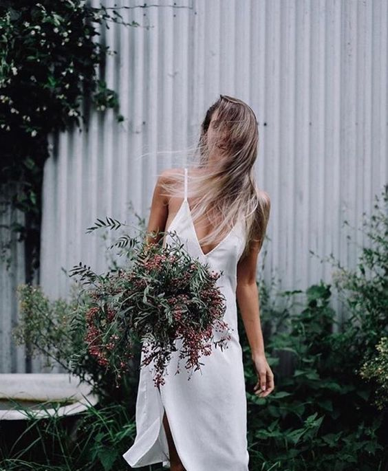 a modern bride in a slip wedding dress, with loose hair and a bouquet of greenery for a relaxed feel