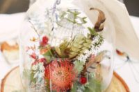 08 a woodland fall wedding centerpiece with feathers, moss, greenery and orange pincushion proteas