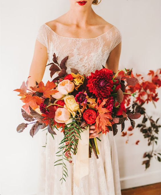 an oversized colorful wedding bouquet with various fall leavesm cascading greenery and bright blooms