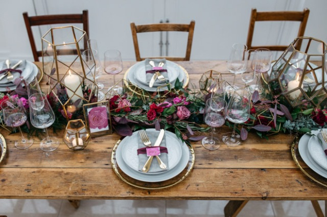The wedding table was styled with a luxurious table runner, lanterns and touches of burgundy and plum