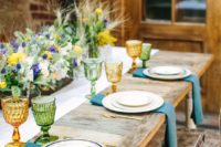 09 a chic rustic setting with colored glasses, blue napkins and a lush floral centerpiece with thistles