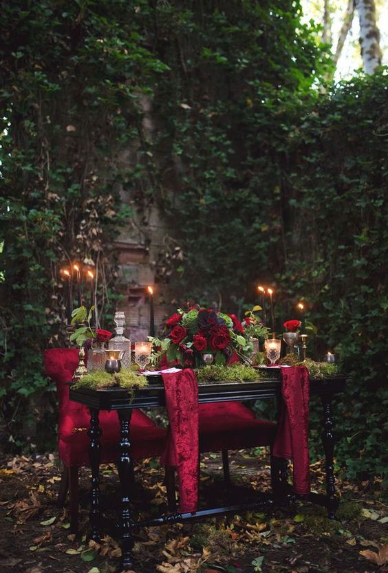 a dark romantic sweetheart table dressed up with moss and burgundy fabric, with greenery and red roses