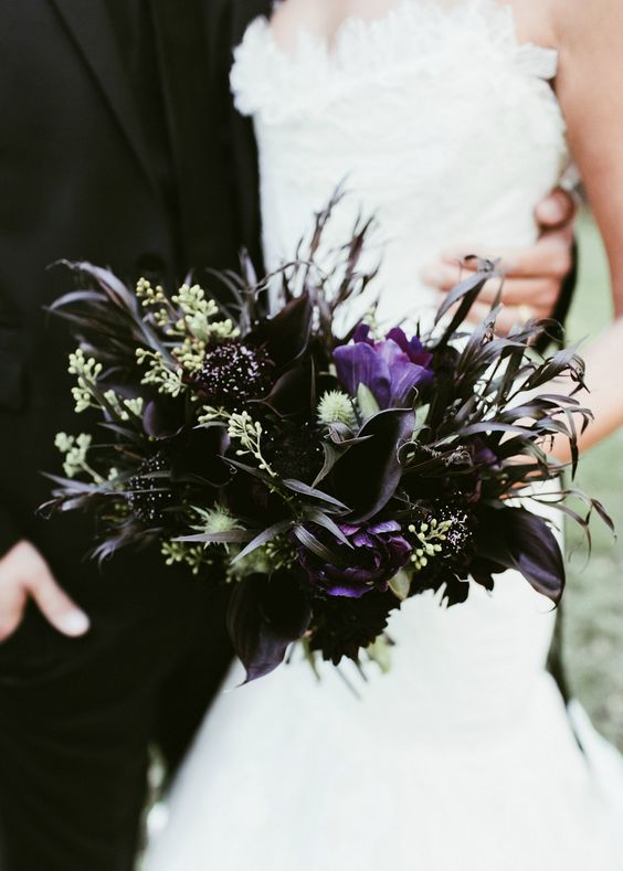 a dark wedding bouquet with black callas and dahlias, greenery and black grasses