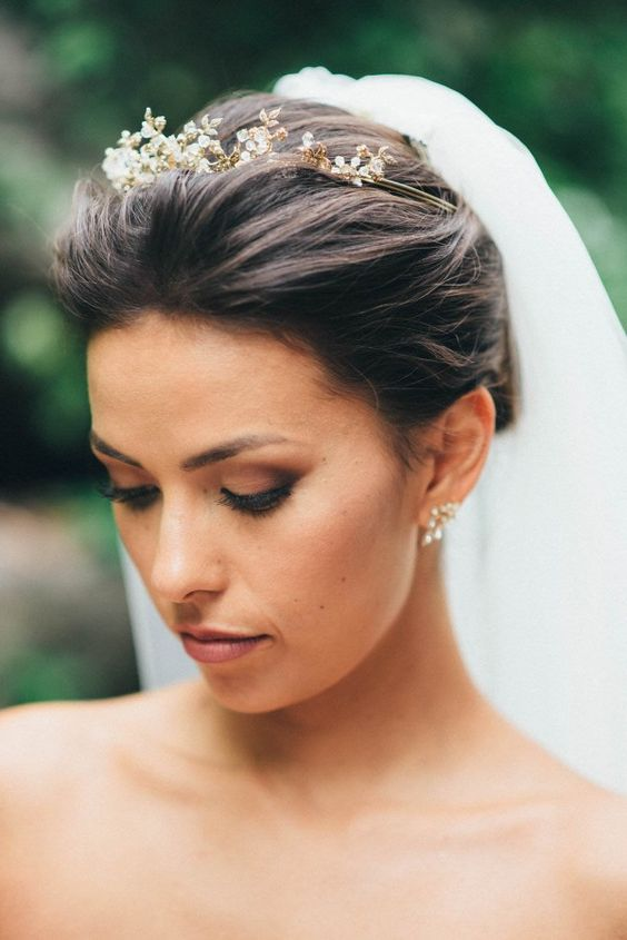 a delicate gold and rhinestone bridal tiara and a long veil for a refined feel