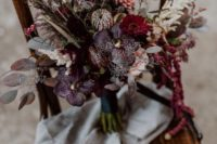 09 a refined dark wedding bouquet done with dark plum, hot pink and pink flowers, colored leaves and herbs for a boho wedding