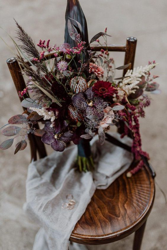 a refined dark wedding bouquet done with dark plum, hot pink and pink flowers, colored leaves and herbs for a boho wedding