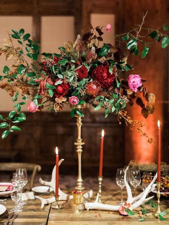 a very elegant fall wedding centerpiece of burgundy and pink blooms, berries and greenery on a tall stand