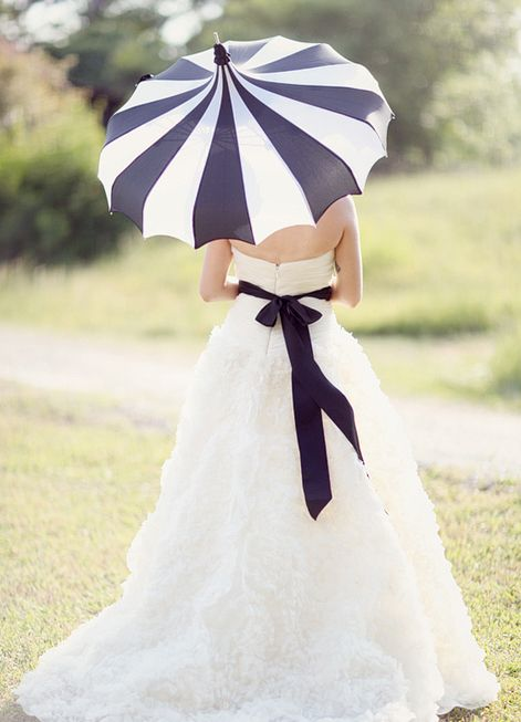 a white dress with a black sash and a matching black and white striped umbrella for a rainy day bride