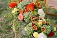 09 rustic floral arrangements in burgundy, red, yellow and white in buckets for a fall rustic wedding
