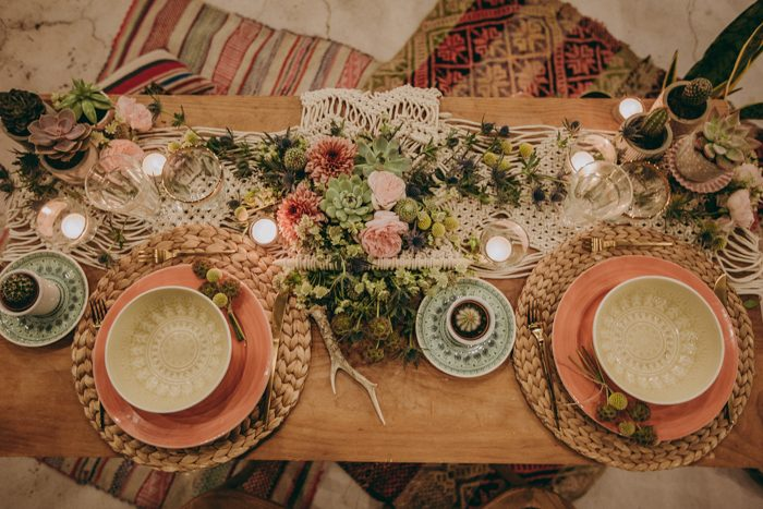 The wedding tablescape was done with a macrame table runner, woven chargers, greenery, flowers and succulents plus candles