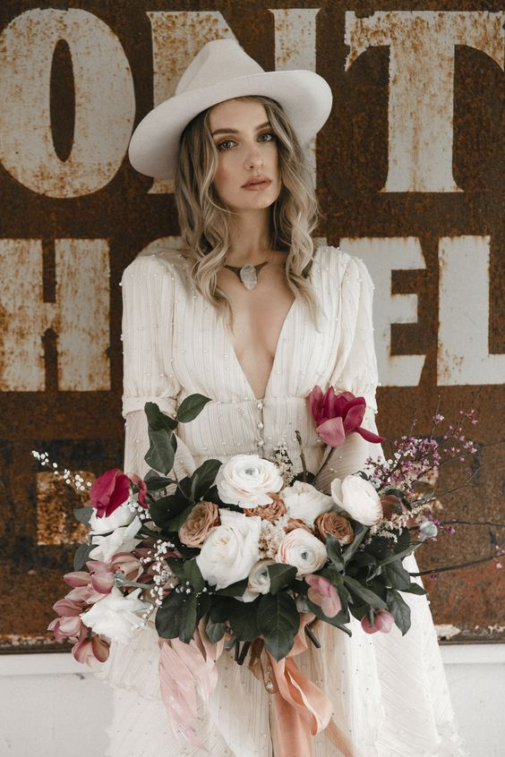a boho wedding dress, a statement necklace and a off-white hat plus lush florals for a wow effect