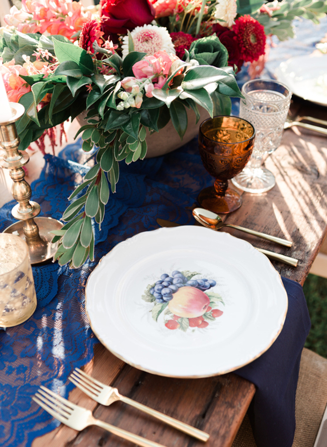 a chic tablescape with a navy lace table runner and napkins and a lush bold floral centerpiece