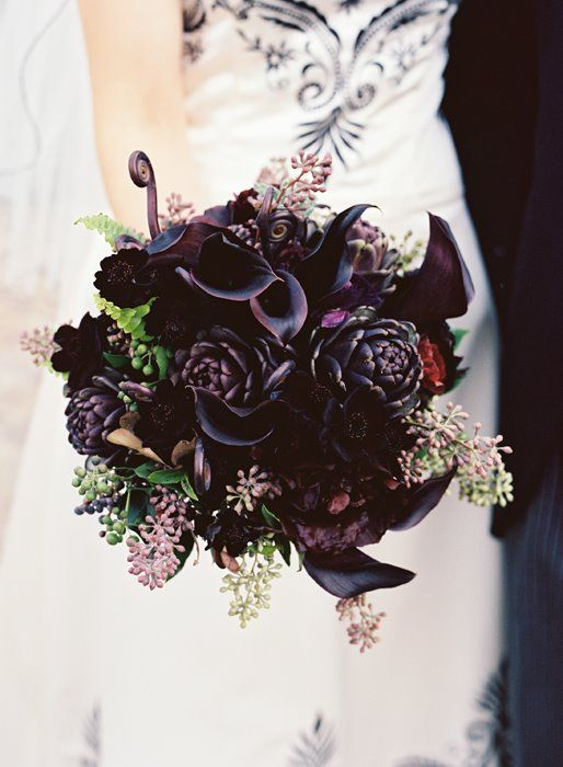 a dark purple bouquet with artichokes, callas, seeded euclayptus and fiddleheads