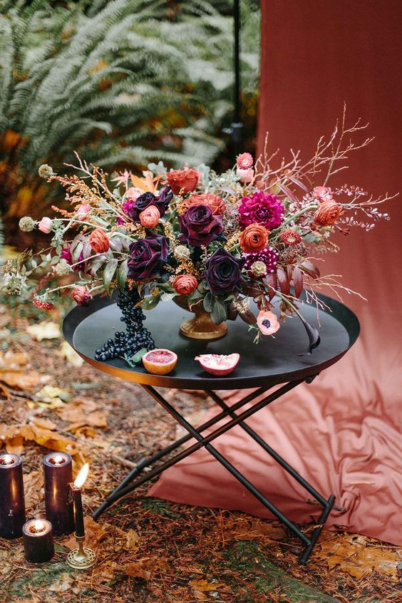 a dark woodland fall wedding centerpiece with branches, herbs and dark and moody blooms