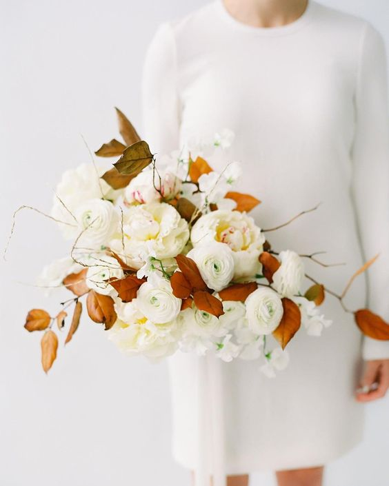 a neutral bridal bouquet with some herbs and rust-colored leaves for a contrast