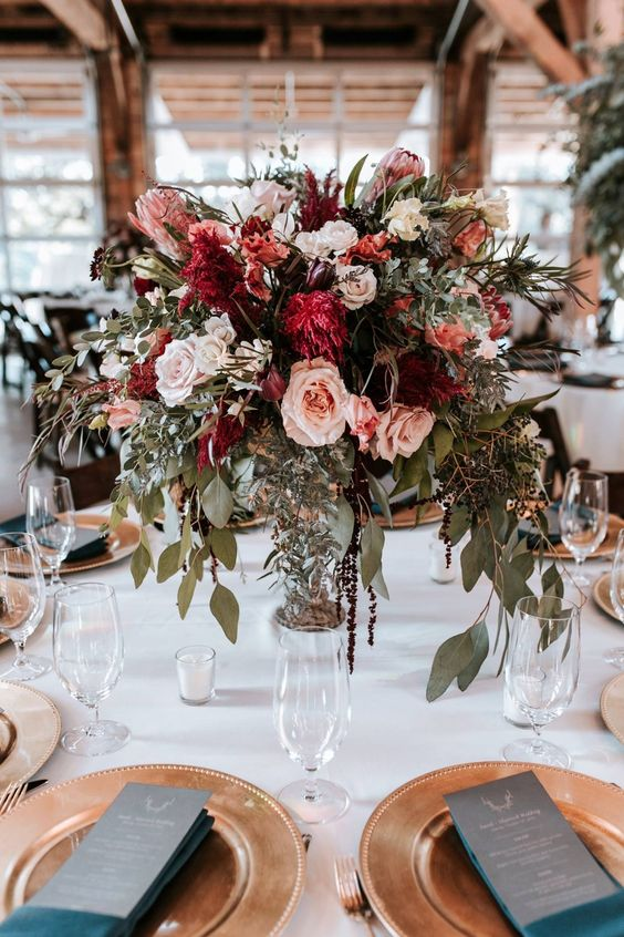 a textural and lush wedding centerpiece of burgundy, blush and white blooms plus cascading greenery