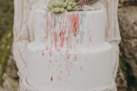 11 The wedding cake was a colorful watercolor one topped with feathers, succulents and macrame