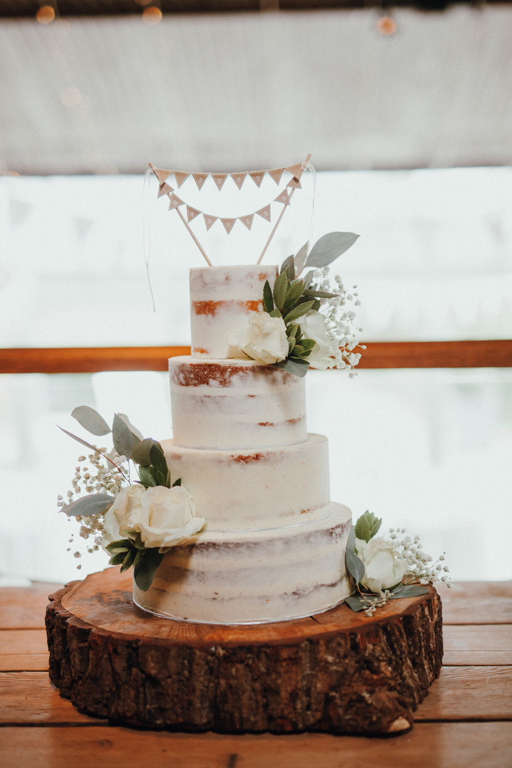 The wedding cake was a naked one, topped with fresh blooms and a bunting topper