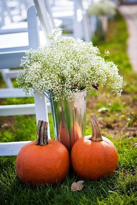 a bucket with baby's breath and a couple of pumpkins for lining up a rustic fall aisle
