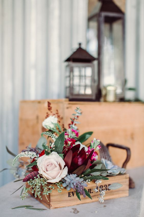 a fall bridal shower centerpiece of a wooden box with bright blooms and textural greenery