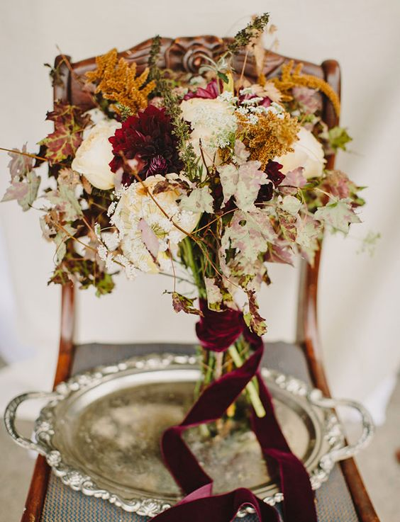 a messy fall wedding bouquet with blush, white and burgundy blooms, herbs and fall leaves plus a burgundy velvet ribbon