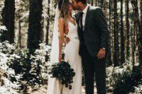 11 a modern slip wedding dress highlighted with an embellished belt, a long veil and a greenery bouquet