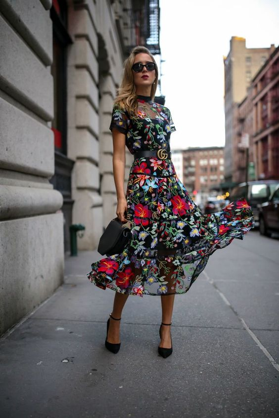 a moody floral midi dress with a sheer bodice and skirt, short sleeves and black shoes and a bag