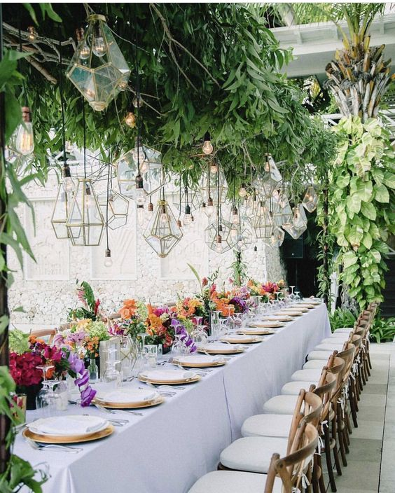 a super lush overhead greenery decoration with lots of bulbs and geometric lanterns hanging