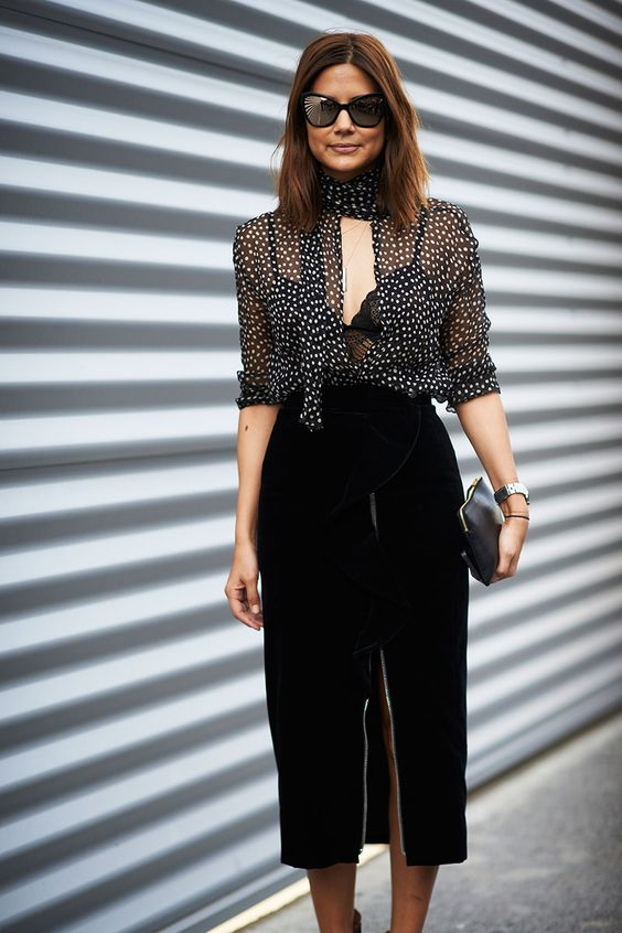 a black lace bralette, a black polka dot sheer blouse, a black velvet pencil skirt with a front slit