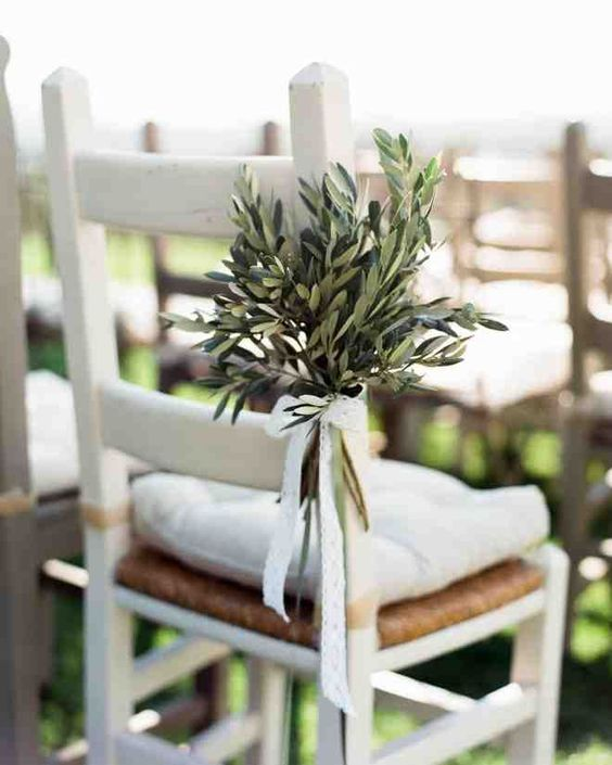 a chic arrangement of olive branches with a white lace bow for a non-typical aisle marker