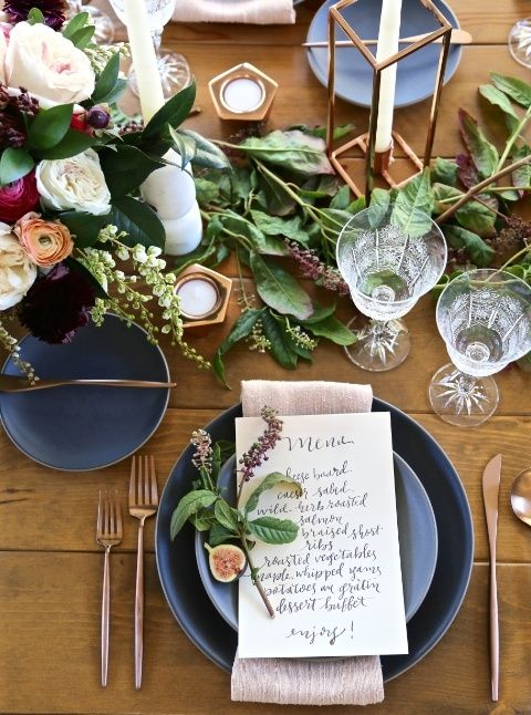a fall bridal shower tablescape with matte grey plates, greenery and lush blooms and gold touches