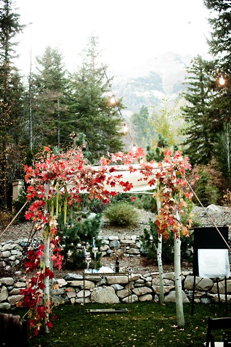 a fall wedding arch decorated with red maple leaves for a colorful statement and a chic look