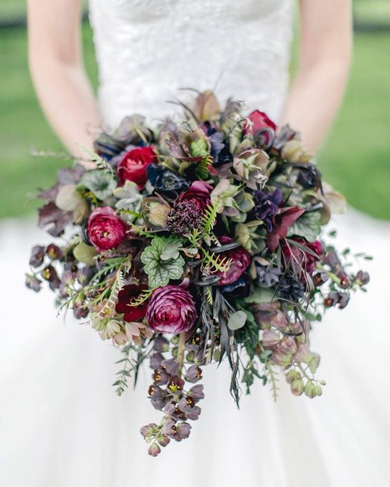 a moody wedding bouquet with purple, burgundy blooms and dark foliage